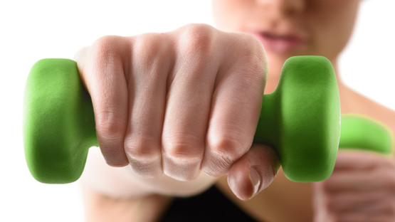 Close up shot of hand by training woman with green dumbbell
